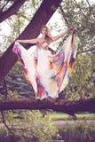 Kobieta w jaskrawym smokingowym lataniu w lesie obrazy stock
