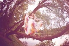 Kobieta w jaskrawym smokingowym lataniu w lesie obraz stock