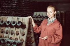 Kobieta w jednolitym działaniu z butelka magazynem dręczy w wytwórnii win cel Obraz Royalty Free