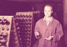 Kobieta w jednolitym działaniu z butelka magazynem dręczy w wytwórnii win cel Zdjęcie Stock
