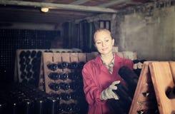 Kobieta w jednolitym działaniu z butelka magazynem dręczy w wytwórnii win cel Obraz Stock