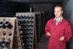 Kobieta w jednolitym działaniu z butelka magazynem dręczy w wytwórnii win cel Zdjęcia Stock