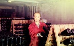 Kobieta w jednolitym działaniu z butelka magazynem dręczy w wytwórnii win cel Zdjęcie Royalty Free