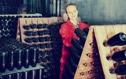 Kobieta w jednolitym działaniu z butelka magazynem dręczy w wytwórnii win cel Obrazy Stock