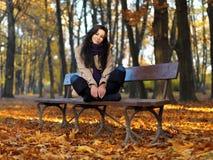 Kobieta w jesieni mody obsiadaniu na ławce obraz royalty free