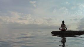 Kobieta w joga lotosowej pozyci wodą przy półmrokiem fotografia stock