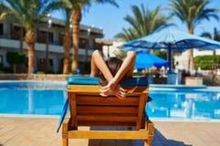 Kobieta w kapeluszowym lying on the beach na lounger blisko basenu przy hotelem, pojęcia lata czas podróżować zdjęcie royalty free