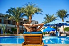 Kobieta w kapeluszowym lying on the beach na lounger blisko basenu przy hotelem, pojęcia lata czas podróżować obraz stock