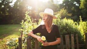 Kobieta w kapeluszu w lato wsi ogródzie zbiory