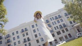 Kobieta w kapeluszu na tle nowożytny budynek z białą fasadą, zbiory wideo