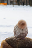 Kobieta w kapeluszu z pompon spojrzeniami przy śniegiem obraz royalty free