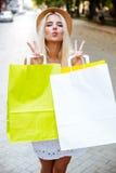 Kobieta w kapeluszy holsing torba na zakupy wysyłać buziaka i Obrazy Royalty Free