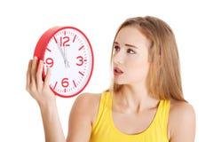Kobieta w koloru żółtego wierzchołku trzyma zegar zdjęcie stock