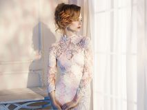 Kobieta w koronki sukni przy okno Zdjęcia Stock