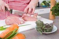 Kobieta w kuchennej kulinarnej pieczonej wieprzowinie: tnący mięso Zdjęcie Royalty Free