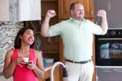 Kobieta w kuchenny patrzeć dokuczający podczas gdy mężczyzna ziewa Zdjęcia Royalty Free