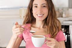 Kobieta w kuchennym mieć kawę z cukierem Zdjęcia Royalty Free
