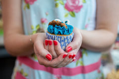 Kobieta w Kwiecistej sukni mienia ciastka potwora babeczce Obrazy Royalty Free