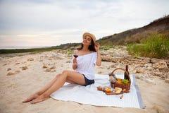 Kobieta w lato pinkinie na plaży przy zmierzchem w białej szkockiej kracie zdjęcie royalty free