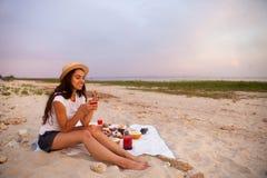 Kobieta w lato pinkinie na plaży przy zmierzchem w białej szkockiej kracie obrazy royalty free