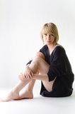 Kobieta w luźny, wielki czarny puloweru siedzieć z ukosa, fotografia stock