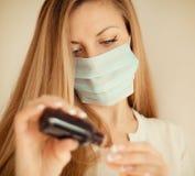 Kobieta w maskowej ręki mienia medycynie fotografia stock