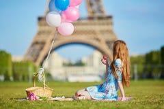 Kobieta w menchiach ubiera z wiązką balony ma pinkin blisko wieży eifla w Paryż zdjęcia stock