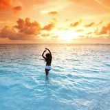 Kobieta w morzu na zmierzchu Zdjęcie Royalty Free