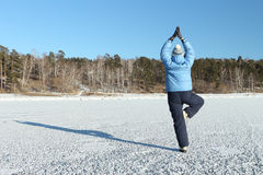 Kobieta w niebieskiej marynarki ćwiczy joga na śnieżystym Obrazy Royalty Free