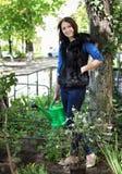 Kobieta w ogrodnictwie nawadnia kwiaty Obrazy Royalty Free