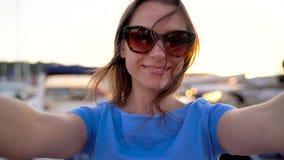 Kobieta w okularach przeciwsłonecznych robi selfie na tle marina z mnóstwo jachtami przy zmierzchem łodziami i, zakończenie up zdjęcie wideo