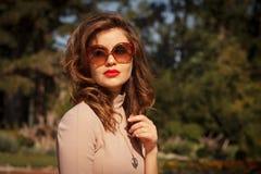 Kobieta w okulary przeciwsłoneczni pozuje plenerowego Obrazy Stock
