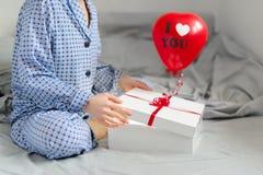 Kobieta w piżamach otwiera prezent to walentynki dni Zdjęcia Stock