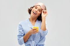 Kobieta w pi?amy i dosypiania masce z sokiem obrazy royalty free