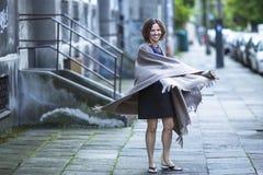 Kobieta w poncho przy wieczór ulicą Szczęśliwy Zdjęcie Royalty Free