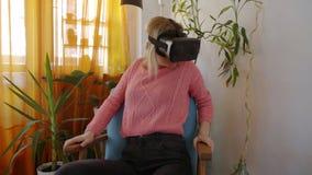 Kobieta w różowym pulowerze w domu straszył używać rzeczywistość wirtualna gogle w nowożytnym karle zbiory