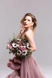 Kobieta w różowej sukni z kwiatu bukietem zdjęcie royalty free
