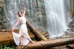 Kobieta w różowym kostiumu stoi bosego na beli, jej ręki jest podwyżką obraz royalty free