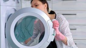 Kobieta w r??owych gumowych r?kawiczkach myje pralk? z p??tnem, siedzi na pod?odze Boczny widok, close-up zbiory