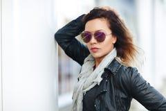 Kobieta w słońc szkłach czarna skórzana kurtka, czarni cajgi pozuje przed odzwierciedlającymi okno Żeński mody pojęcie plenerowy Fotografia Stock