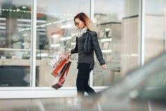 Kobieta w słońc szkłach czarna skórzana kurtka, czarni cajgi z torba na zakupy, cieszy się spacer przed odzwierciedlającym sklepu Fotografia Stock