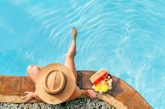 Kobieta w słomianego kapeluszu obsiadaniu na basen stronie z talerzem tropikalne owoc Odgórnego widoku strzał obrazy stock