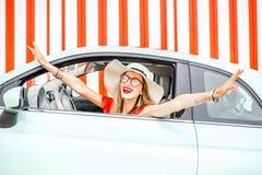 Kobieta w samochodzie na czerwieni ściany tle fotografia royalty free