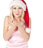 Kobieta w Santa Claus kapeluszu ciosach na otwartych rękach obraz royalty free