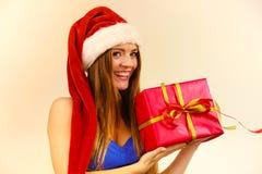 Kobieta w Santa Claus kapeluszu trzyma prezenta pudełko Święta tła blisko czerwony czasu obraz royalty free