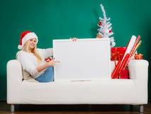 Kobieta w Santa kapeluszowego mienia pustego miejsca białej desce Zdjęcia Stock