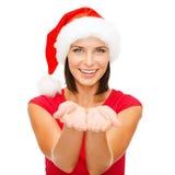 Kobieta w Santa pomagiera kapeluszu z coś na palmach obrazy stock