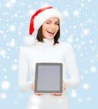 Kobieta w Santa pomagiera kapeluszu z pastylka komputerem osobistym Zdjęcia Royalty Free