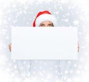 Kobieta w Santa pomagiera kapeluszu z pustą białą deską Obraz Stock