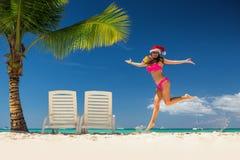 Kobieta w Santa ` s kapeluszowy relaksować na tropikalnej plaży Obraz Stock
